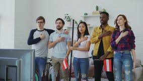 Wielo- grupa etnicza przyjaciele słucha Austriackiego hymn państwowego i śpiewa bawi się mistrzostwo na TV przed oglądać zbiory wideo