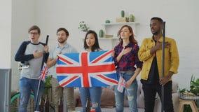 Wielo- grupa etnicza przyjaciele słucha Brytyjskiego hymn państwowego i śpiewa bawi się mistrzostwo na TV przed oglądać zbiory