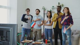 Wielo- grupa etnicza przyjaciele słucha Holenderskiego hymn państwowego i śpiewa bawi się mistrzostwo na TV przed oglądać zbiory