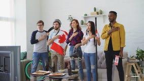 Wielo- grupa etnicza przyjaciele słucha krajowego Kanadyjskiego hymn i śpiewa bawi się mistrzostwo na TV przed oglądać zdjęcie wideo