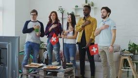 Wielo- grupa etnicza przyjaciele słucha Szwajcarskiego hymn państwowego i śpiewa bawi się mistrzostwo na TV przed oglądać zdjęcie wideo