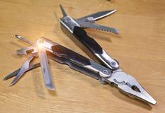 Wielo- narzędzie jest kieszeniowym wmarszem z wystawiającymi narzędziami na drewnianym stole i krawędziami Zdjęcia Royalty Free