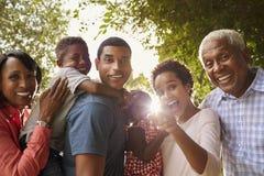 Wielo- pokolenia czerni rodzina w ogrodowym spojrzeniu kamera Zdjęcia Royalty Free