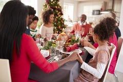 Wielo- pokolenie mieszać biegowe rodzinne mienie ręki i mówić przy Bożenarodzeniowym obiadowym stołem gracja, boczny widok zdjęcia stock