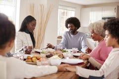 Wielo- pokolenie mieszać mienie ręki, biegowa rodzinna mówić przed jeść ich Niedziela gościa restauracji gracja i zdjęcie stock