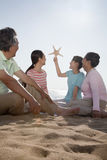 Wielo- pokoleniowy rodzinny obsiadanie na plaży patrzeje rozgwiazdy Fotografia Royalty Free