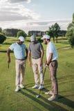 Wieloetniczna grupa golfiści trzyma kluby i opowiada podczas gdy stojący zdjęcie royalty free