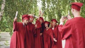 Wieloetniczna grupa kończyć studia uczni pozuje dla smartphone kamery, macha ręki z dyplomami i krzyczy, podczas gdy zdjęcie wideo