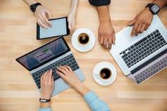 Wieloetniczna grupa młodzi ludzie używa laptopy i pijący kawę fotografia royalty free