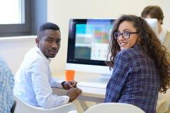 Wieloetniczna grupa szczęśliwi ludzie biznesu pracuje z laptopem w biurze obraz stock