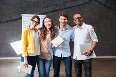 Wieloetniczna grupa szczęśliwi młodzi ludzie biznesu stoi w biurze Zdjęcia Stock