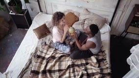 Wieloetniczna para siedzi na łóżku i przekręca kulę ziemską Mężczyzna i kobieta podnosimy miejsce przeznaczenia podróżować, ścisk Obraz Stock