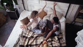 Wieloetniczna para siedzi na łóżku i przekręca kulę ziemską Mężczyzna i kobieta podnosimy miejsce przeznaczenia podróżować, ścisk Zdjęcia Royalty Free