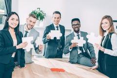 wieloetniczni biznesmeni trzyma łamigłówka kawałki wpólnie fotografia royalty free