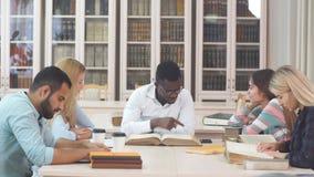 Wieloetniczni młodzi ludzie siedzi przy stołowymi czytelniczymi odniesienie książkami dla nauk notatek Grupa młodzi ucznie robi s zbiory