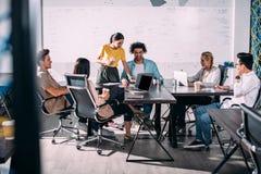 wieloetniczni partnery biznesowi ma spotkania przy stołem z laptopami w nowożytnym obraz stock