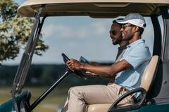 Wieloetniczni przyjaciele opowiada podczas gdy jeździecka golfowa fura Zdjęcia Royalty Free