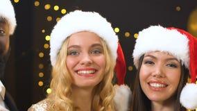 Wieloetniczni przyjaciele trzyma szampański i patrzeje kamera w Santa kapeluszach, niecka zbiory wideo