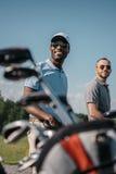 Wieloetniczni sportowowie iść pole golfowe, torba z klubami na przedpolu Obraz Royalty Free