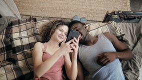 Wieloetniczny pary lying on the beach na łóżku i używać smartphone Mężczyzna i kobieta szczęśliwi wpólnie Samiec i żeński śmiać s zdjęcie wideo