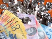 Wielokrotność pięćdziesiąt dolarów australijskich notatek na przodzie stos połyskiwać monety Obrazy Stock