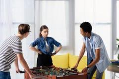 wielokulturowe nastoletnie chłopiec bawić się stołową futbolu i kobiety przyjaciela pozycję z rękami akimbo zdjęcia stock