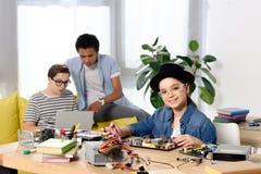 wielokulturowe nastoletnie chłopiec używa laptop i żeńską dzieciaka naprawiania komputeru płytę główną zdjęcie royalty free