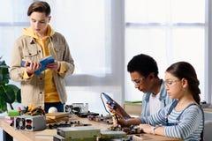 wielokulturowi nastolatkowie lutuje komputerowego obwód z lutowniczym żelazem i przyjacielem zdjęcie stock