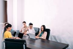 wielokulturowi partnery biznesowi ma spotkania przy stołem z laptopami w nowożytnym obraz stock