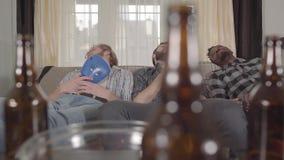 Wielokulturowi przyjaciele śpi na kanapie po oglądać boksować na TV Opróżnia piwne butelki i układu scalonego puchar jest  zdjęcie wideo