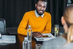 wielokulturowy biznesmen i bizneswoman patrzeje each inny przy stołem fotografia royalty free