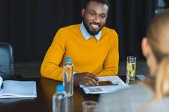 wielokulturowy biznesmen i bizneswoman patrzeje each inny przy stołem zdjęcie royalty free