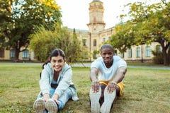 Wielokulturowy pary rozciąganie na trawie przy obraz royalty free