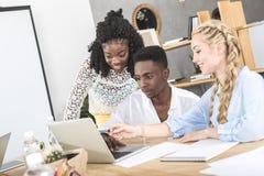 wielokulturowy uśmiechnięty biznesmen i bizneswomany używa laptop przy miejscem pracy obrazy stock