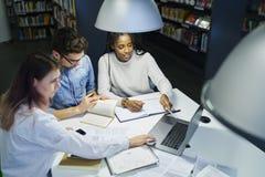 Wielonarodowa drużyna szkoła biznesu ucznie siedzi przy desktop w bibliotece uniwersyteckiej fotografia stock