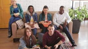 Wielonarodowa grupa młodzi przyjaciele bawić się tv grę zbiory