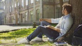 Wielonarodowy faceta obsiadanie pod drzewem z książką, patrzeje z ukosa, wolny czas Obrazy Stock