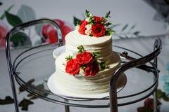 wielopoziomowy ślubny tort z czerwonymi różami na szklanej tacy obrazy stock