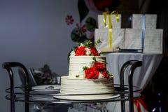 Wielopoziomowy biały tort z różami na szklanej tacy przeciw prezentom zdjęcie stock