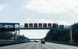 Wieloskładnikowi znaki ostrzegawczy nad autobahn zwalniają puszków roadworks zdjęcia royalty free