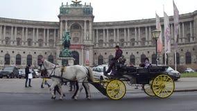 WIEN, ÖSTERREICH - DEZEMBER, 24 Retro- Pferdekutsche gegen österreichische Nationalbibliothek auf Heldenplatz populär Stockfoto