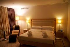 WIEN ÖSTERRIKE - APRIL 30th, 2017: Konungen storleksanpassade säng i ett lyxigt hotellrum med en vardagsrumstol på takvåningfölje royaltyfri foto
