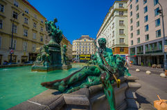 Wien Österrike - 11 Augusti, 2015: Den mycket trevliga springbrunnen med statyer och härligt grönt vatten lokaliserade centret, G Arkivbild