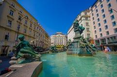 Wien Österrike - 11 Augusti, 2015: Den mycket trevliga springbrunnen med statyer och härligt grönt vatten lokaliserade centret, G Royaltyfri Bild