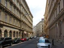 Wien Österrike - Augusti 3, 2014: en sikt för sidogata med parkerade bilar och barockbyggnader i centrala Wien nära Burggartenen Royaltyfri Foto