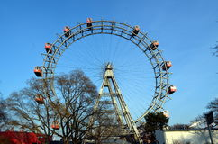 WIEN ÖSTERRIKE - MARS 18, 2016: Den röda kabinen av äldsta Ferris Wheel i Prater parkerar på himmelbakgrund Wien Prater Wurstelpr Arkivfoto