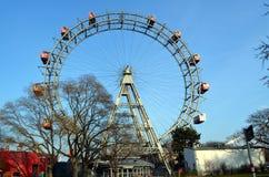 WIEN ÖSTERRIKE - MARS 18, 2016: Den röda kabinen av äldsta Ferris Wheel i Prater parkerar på himmelbakgrund Wien Prater Wurstelpr Royaltyfri Fotografi