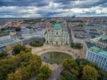 WIEN ÖSTERRIKE - OKTOBER 05, 2016: Den Wien Karlskirche kyrkan med Resselpark parkerar och molnig himmel Kyrka för St Charles ` s Royaltyfria Bilder