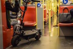 Wien Österrike - September, 16, 2019: Folket, en motoriserad sparkcykel och hundkapplöpningen är passagerare inom en Wien gångtun arkivbild