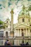 Wien Österrike - September, 15, 2019: Wien Karlskirche kyrka med Resselpark att parkera och folk som omkring kopplar av royaltyfri foto